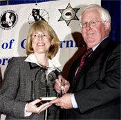 Coordinator Debora McGlynn (left) accepts her award from POST Commission Chairman Jim Fox
