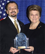 Dean Gialamas, Director of the Forensic Science Services Division (left), accepts the award for the Orange County Sheriff's Department's PEBT Program from POST Commission Chair Collene Campbell
